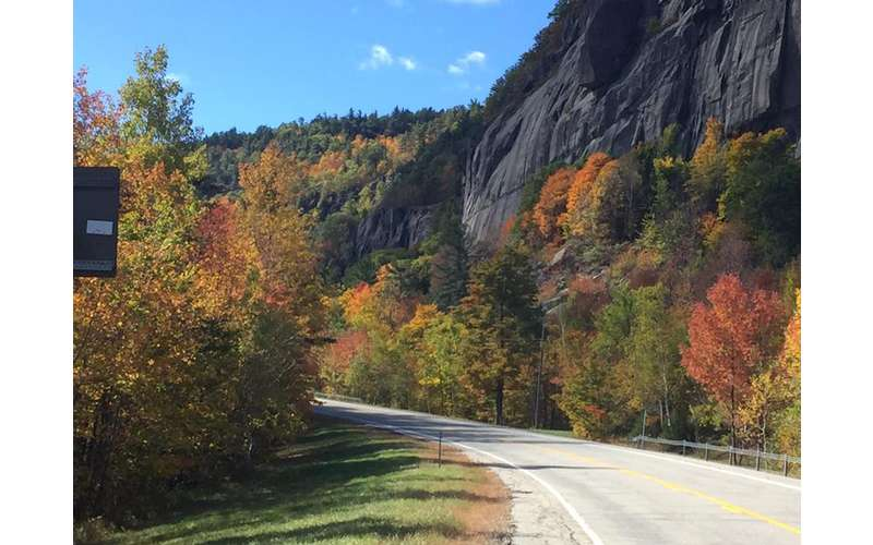 a road along the mountainside with colorful trees during fall