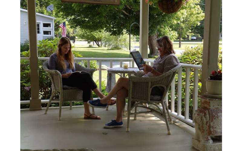 two women in chairs reading outdoors on a porch