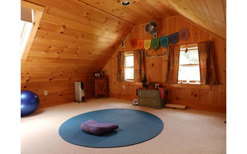 a room with wooden walls and a round yoga mat