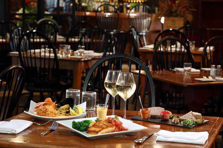 restaurant table with multiple plates of food and two glasses of white wine