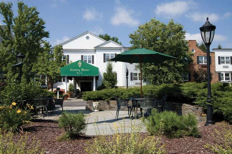 green century house awning with two patio tables and one green patio umbrella in front of it
