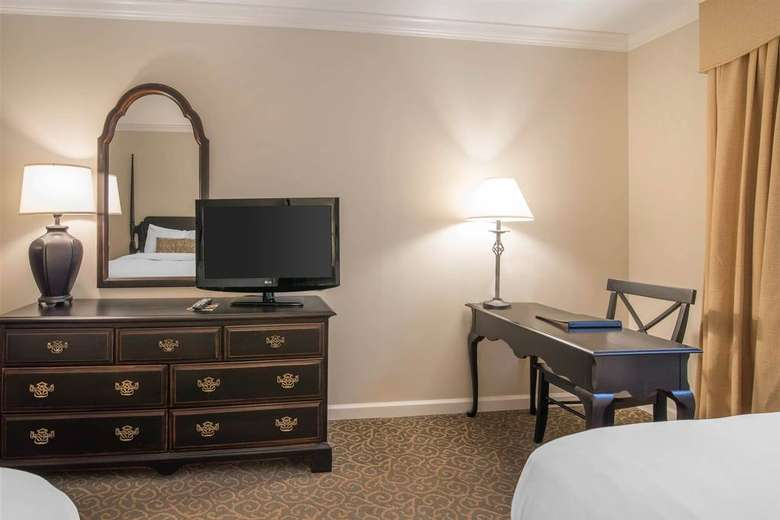 dresser, tv, and desk in a hotel room