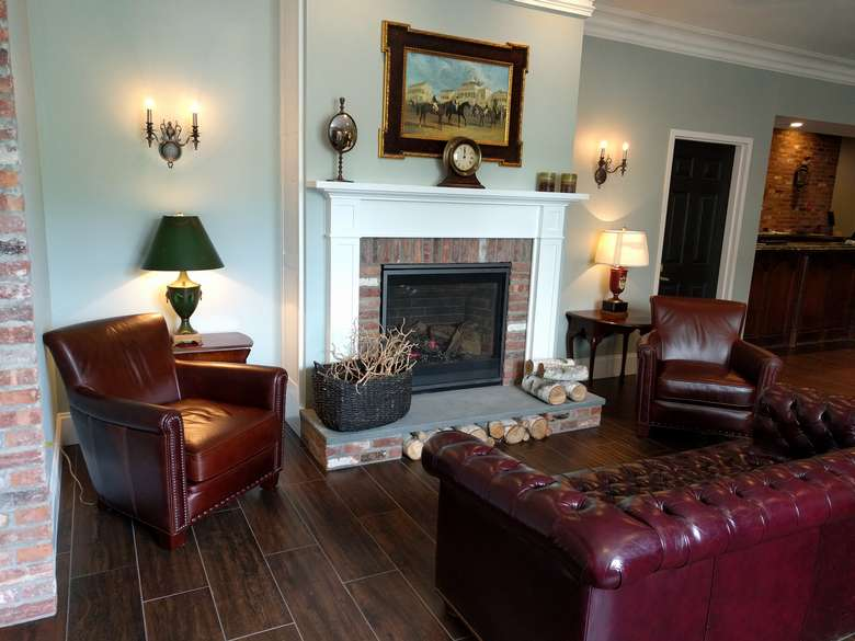 leather couches and chairs in front of a fireplace