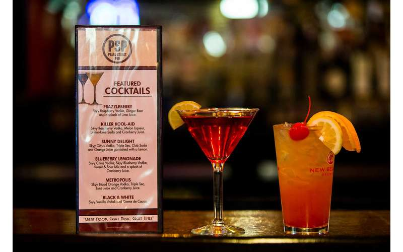 two cocktails next to a cocktail menu