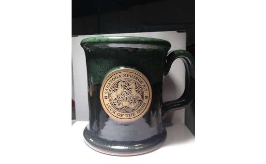 dark green coffee mug with a gold circle that says saratoga springs ny luck of the irish