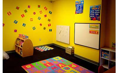 a room with a floor puzzle, games, block letters on the wall, and bright yellow walls
