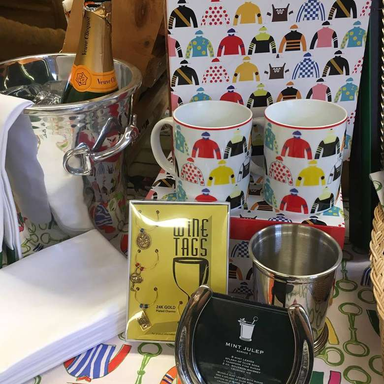 two mugs with jockey designs on them, plus a box of wine tags for sale in a store