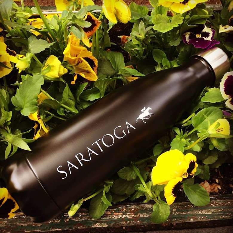 black stainless steel water bottle with saratoga and a horse/jockey on it sitting in a patch of flowers