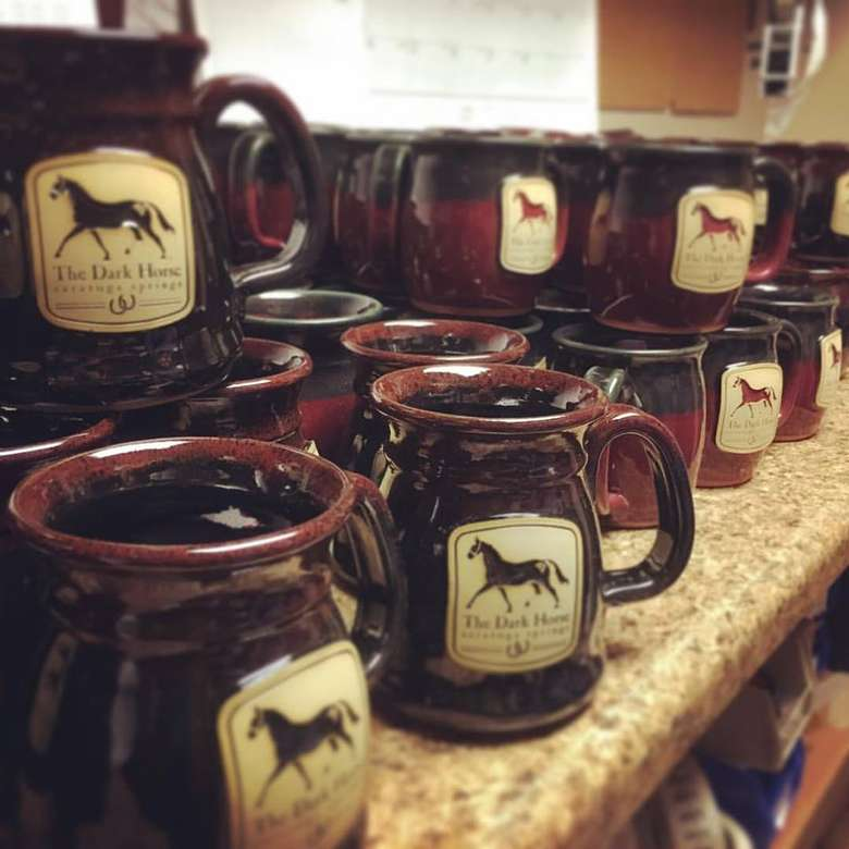 ceramic coffee mugs with a black horse and text that says the dark horse on them