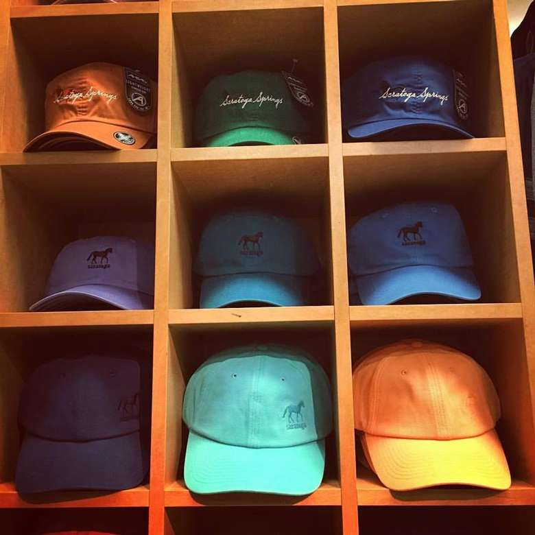 nine shelves, each with a colorful baseball hat on it