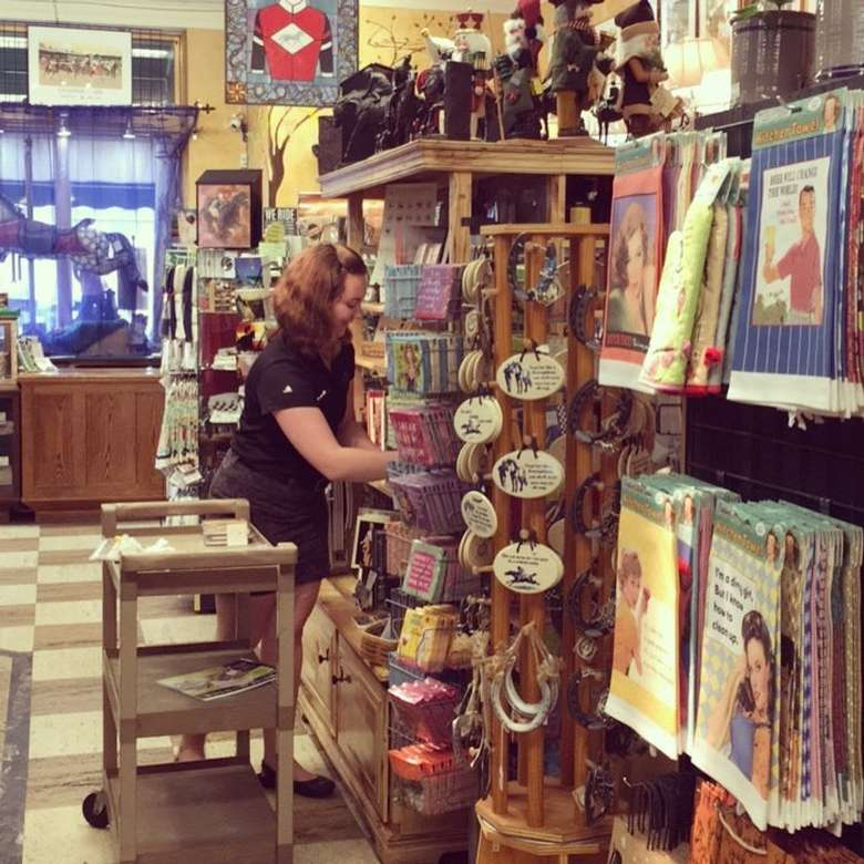 woman re-stocking products in a saratoga souvenir store