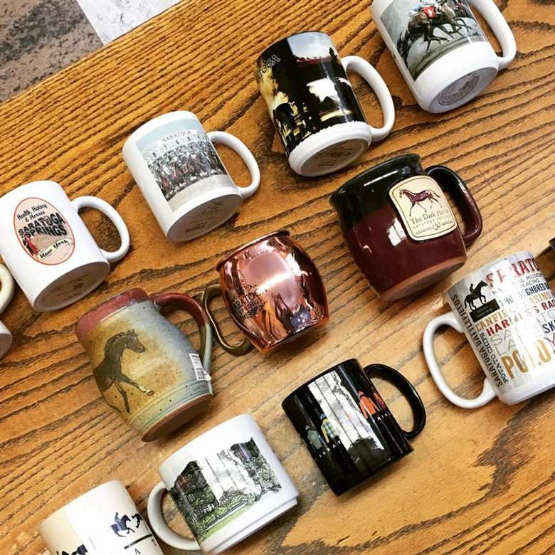 11 coffee mugs with different horse and saratoga designs on them