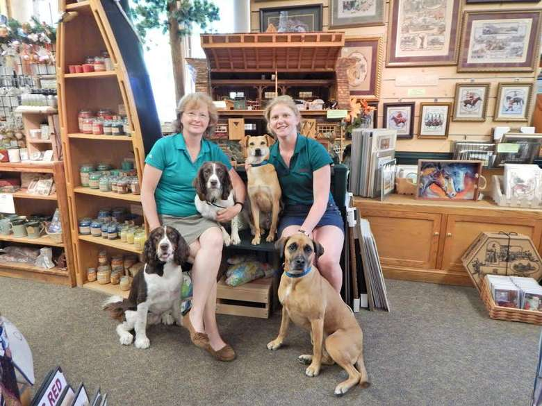 two women in green polo shirts posing with four dogs
