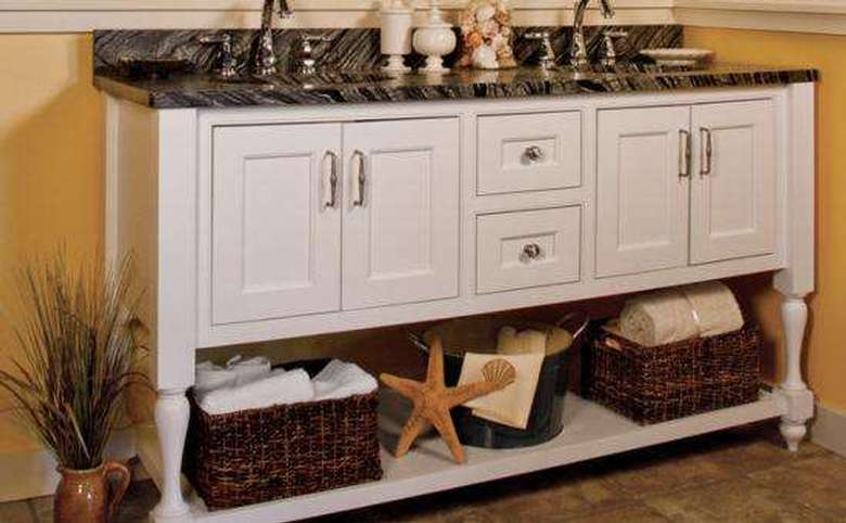 a wide sink with white cabinet doors