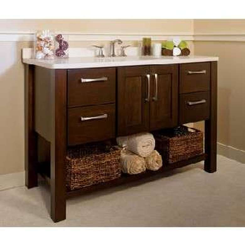 a small sink with brown cabinet doors