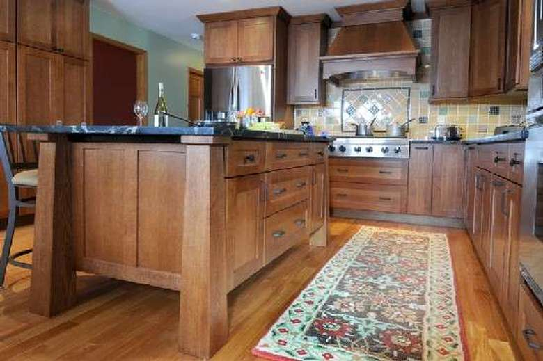 brown cabinets in a kitchen with a long rug on the floor