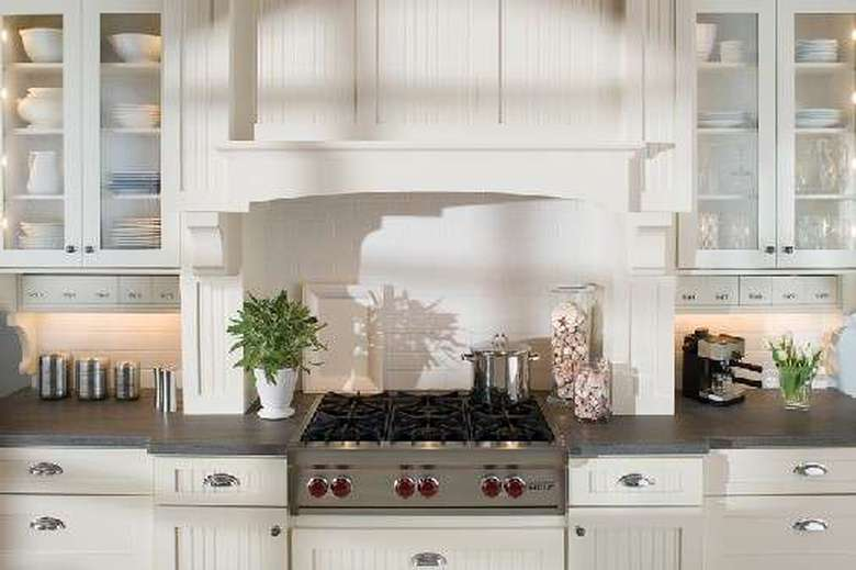 the stovetop in a kitchen with white cabinets around it