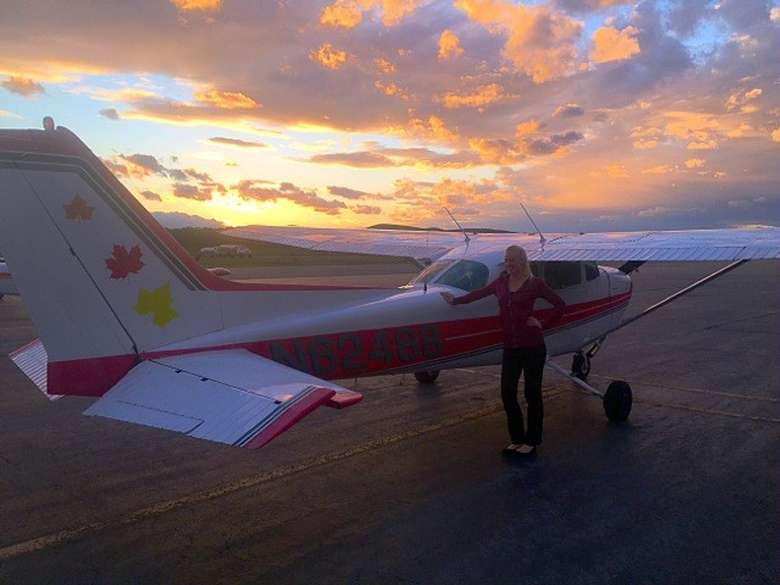 woman standing next to a small plane at sunset