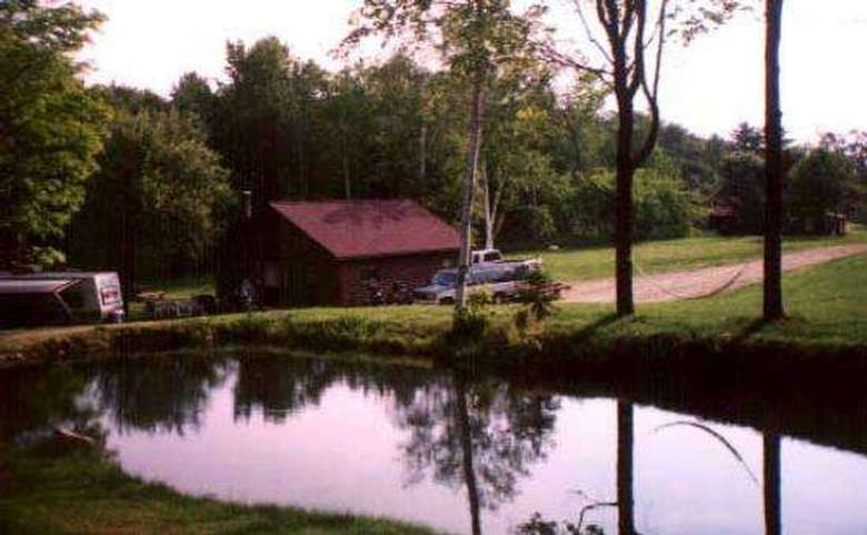 a brown cabin located near a calm pond