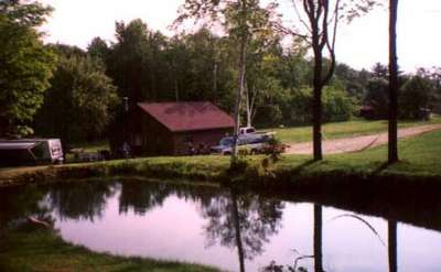 a brown cabin located near a calm pond