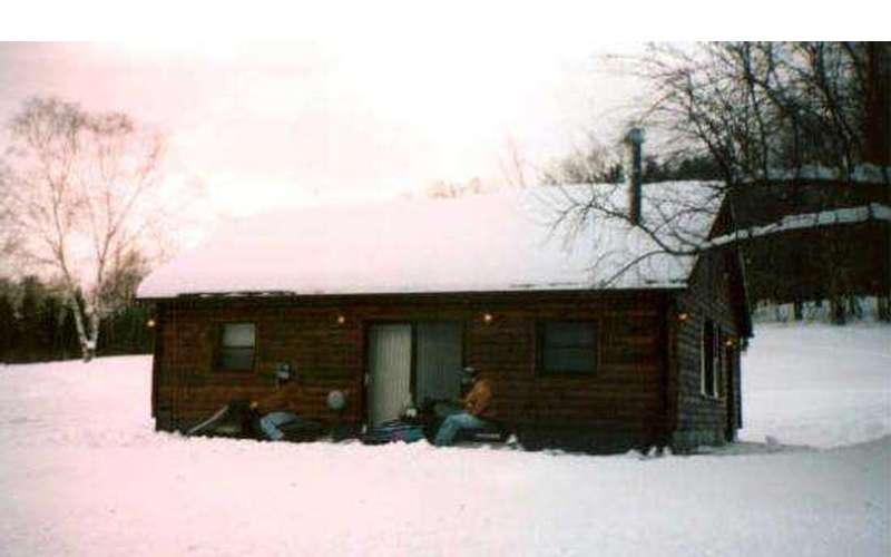 a brown cabin covered in snow