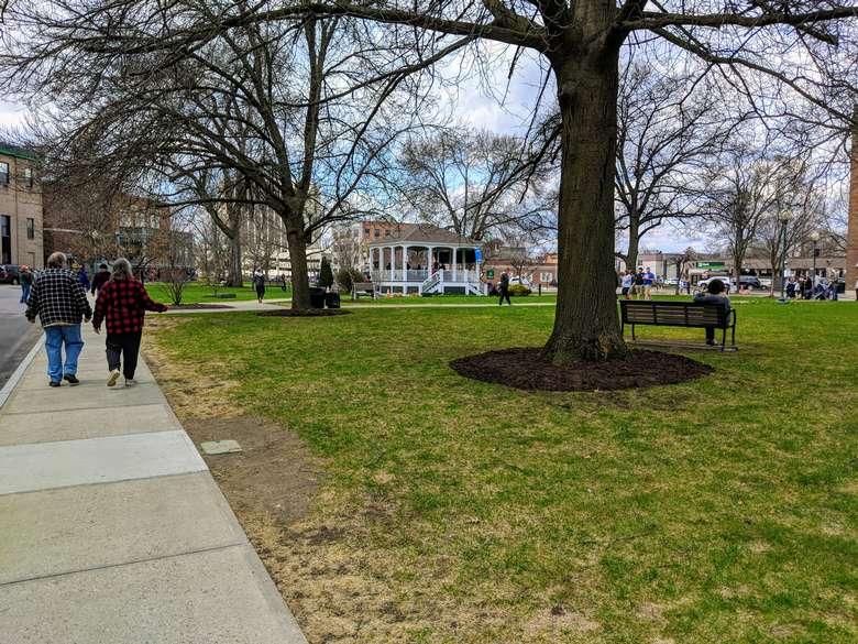 people walking around park, trees, benches, gazebo