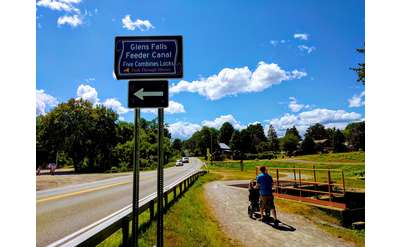 Feeder Canal trail sign, person walking with stroller