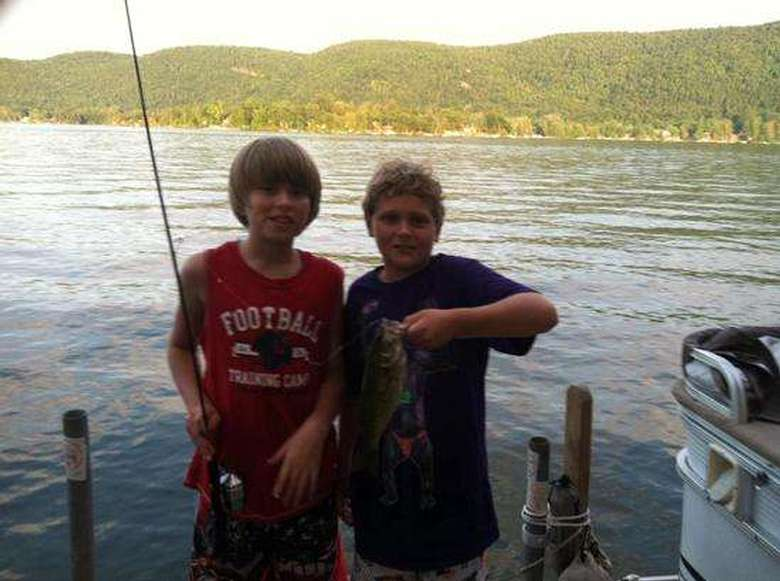 two young boys, one with fishing pole and the other holding a fish