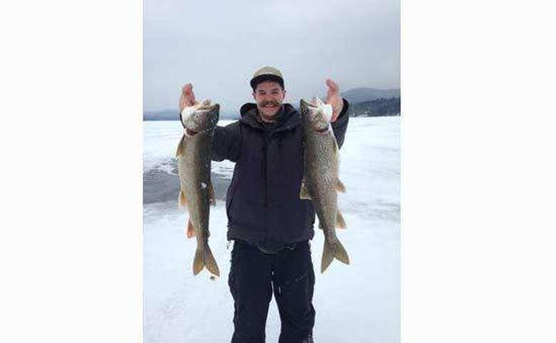 fisherman holding up two fish on frozen lake