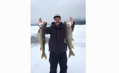 fisherman holding up two fish on frozen lake