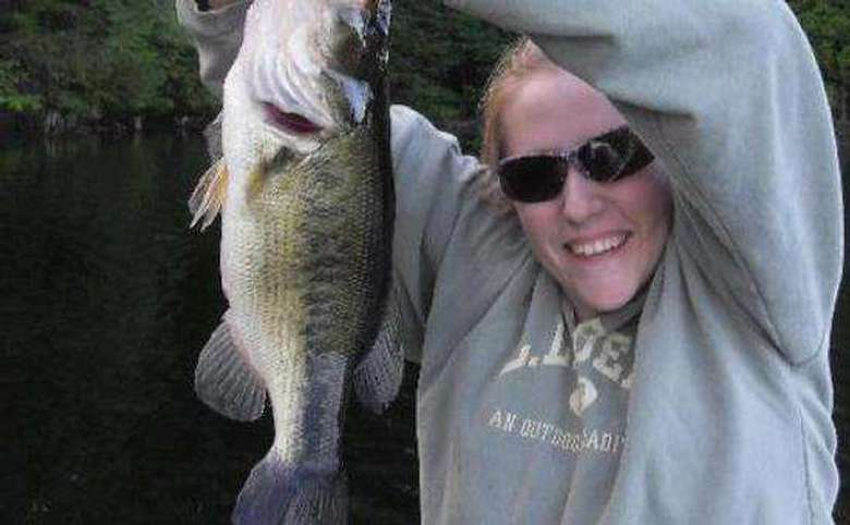 woman holding up fish caught at lincoln pond