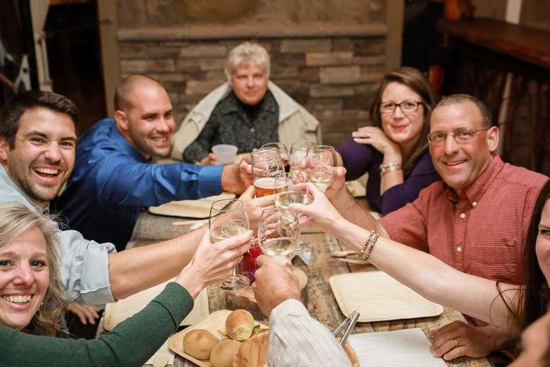 group of people raising glasses at a table