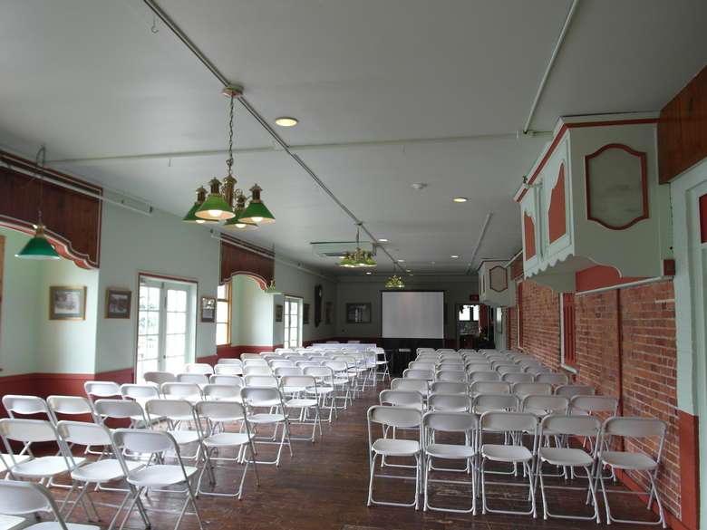 room set up for a presentation with rows of chairs and a projector screen