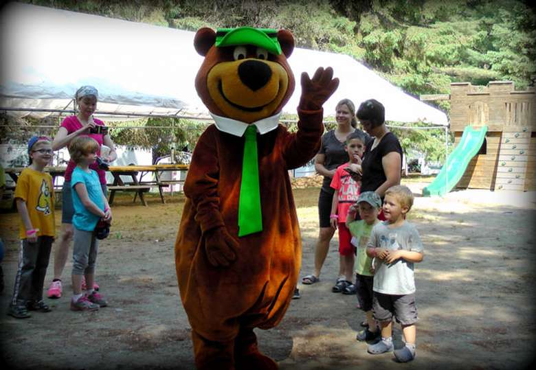 Yogi bear waving, surrounded by kids