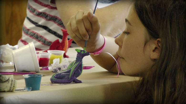 a little girl painting what looks like a ceramic dragon