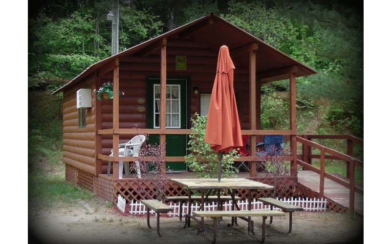 a cabin with a picnic table in front and a deck