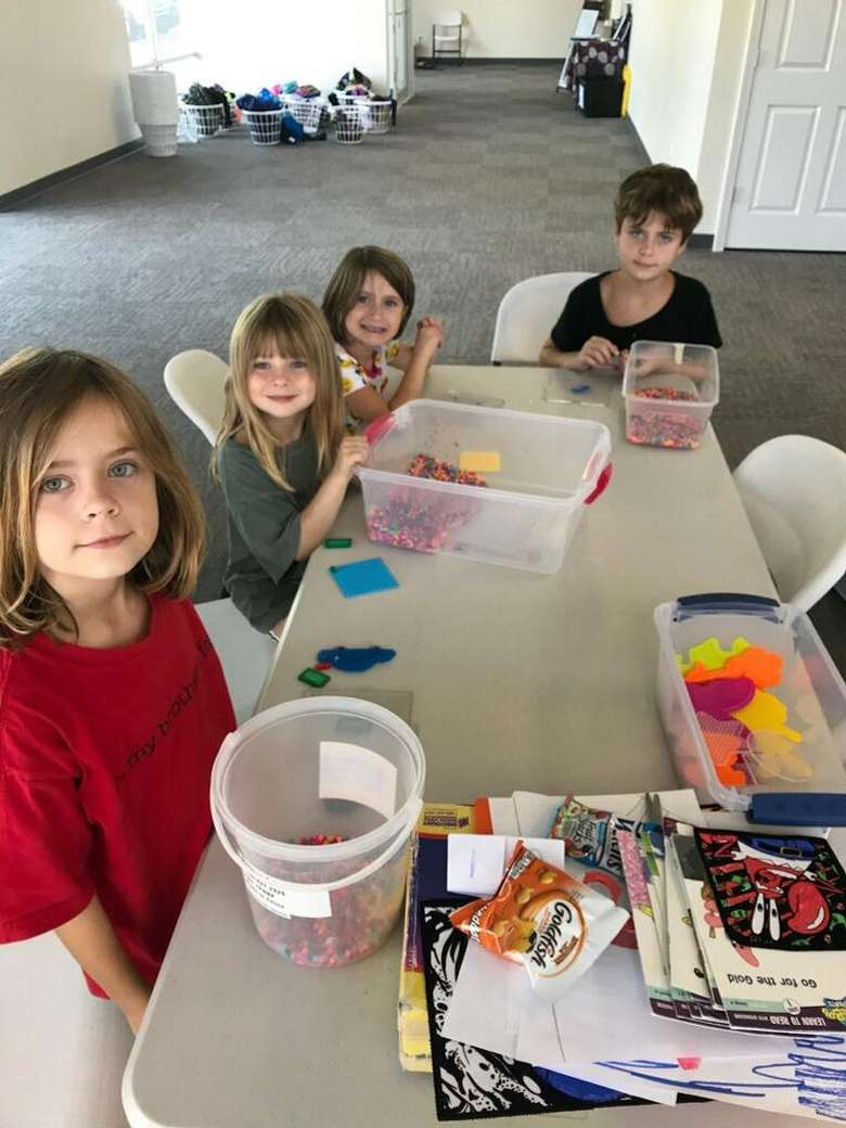 group of kids at a table with crafts