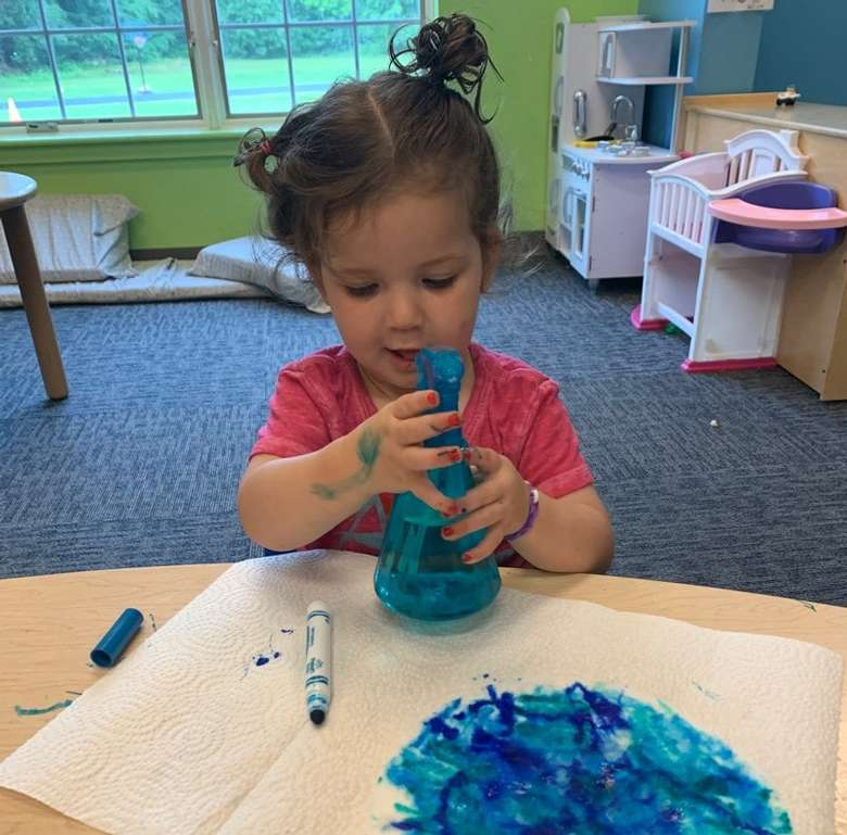 girl playing with blue object