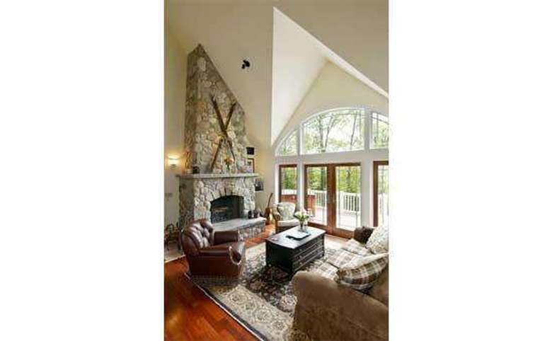 family room with a large stone fireplace and big windows