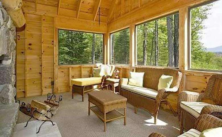 three season porch with wooden walls and a stone fireplace