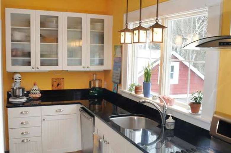 kitchen with yellow walls and a black stone counter top