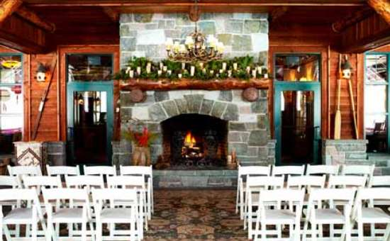 a small number of white chairs set up for a wedding ceremony in front of a stone fireplace