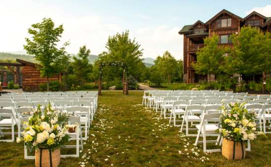 rows of white chairs set up for an outdoor wedding ceremony