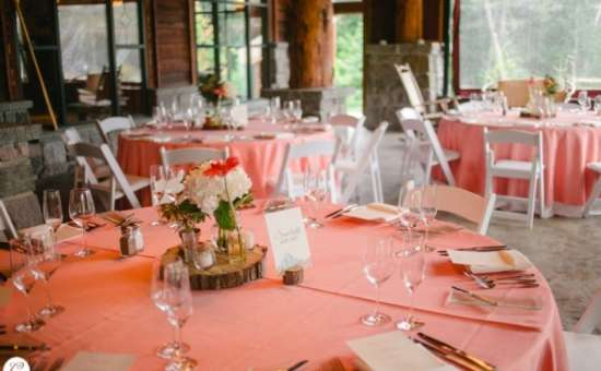 wedding reception tables decorated with peach tablecloths