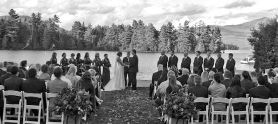 black and white photo of an outdoor wedding on the shore of a lake