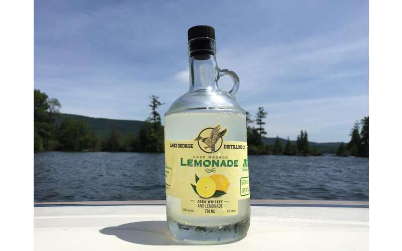 a bottle of Lake George Lemonade with the lake in the background