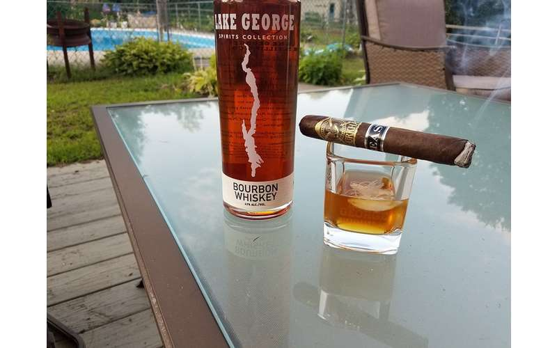a glass of bourbon whiskey on a table with a cigar on it and the whiskey bottle next to it