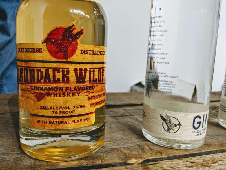 a bottle of Adirondack Wildfire Whiskey next to a bottle of gin