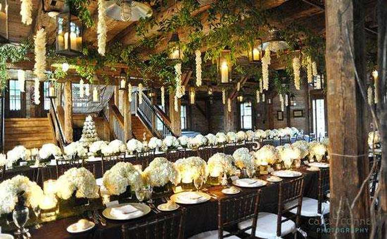 tables decorated for a formal occasion with large floral centerpieces and flowers hanging from the ceiling