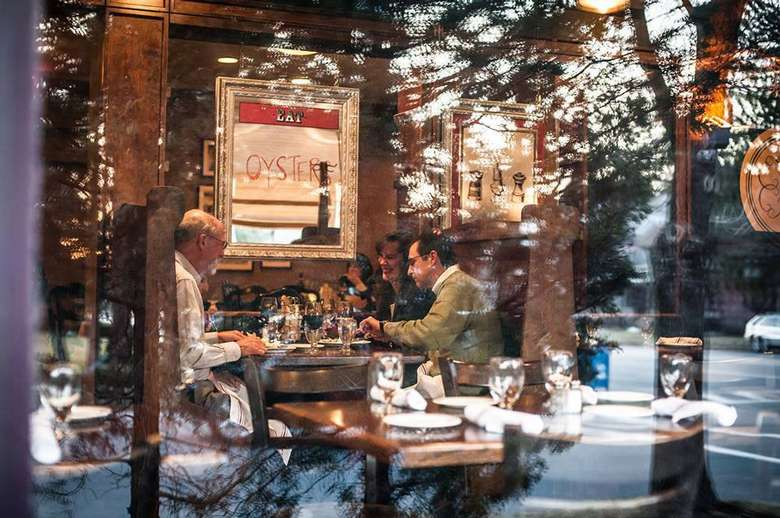 people dining in the brook tavern as seen through the front window